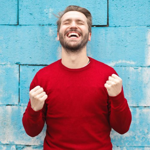 Man in red sweater cheering in front of a blue brick wall
